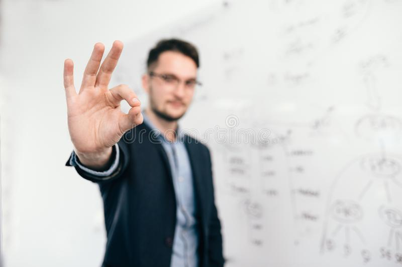 Young dark-haired man in glasses is standing near whiteboard in office. He wears blue shirt and dark jacket. Focus on royalty free stock photo