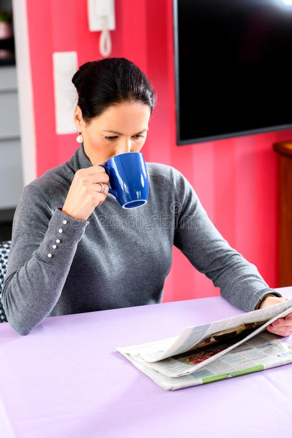 Young woman at home with cup of coffeee relaxing. Young dark haired woman at home with cup of coffeee reading newspaper stock photo