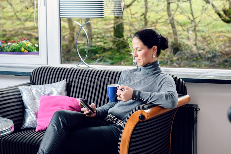 Young woman at home with cup of coffeee relaxing. Young dark haired woman at home with cup of coffeee relaxing royalty free stock image