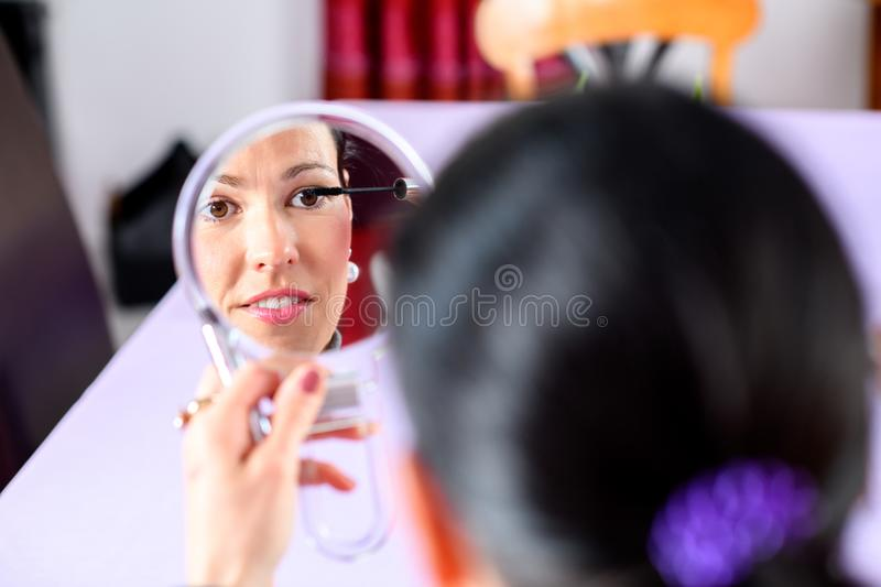 Dark haired woman looking in mirror and applying make up. Young dark haired woman looking in mirror and applying make up royalty free stock photos