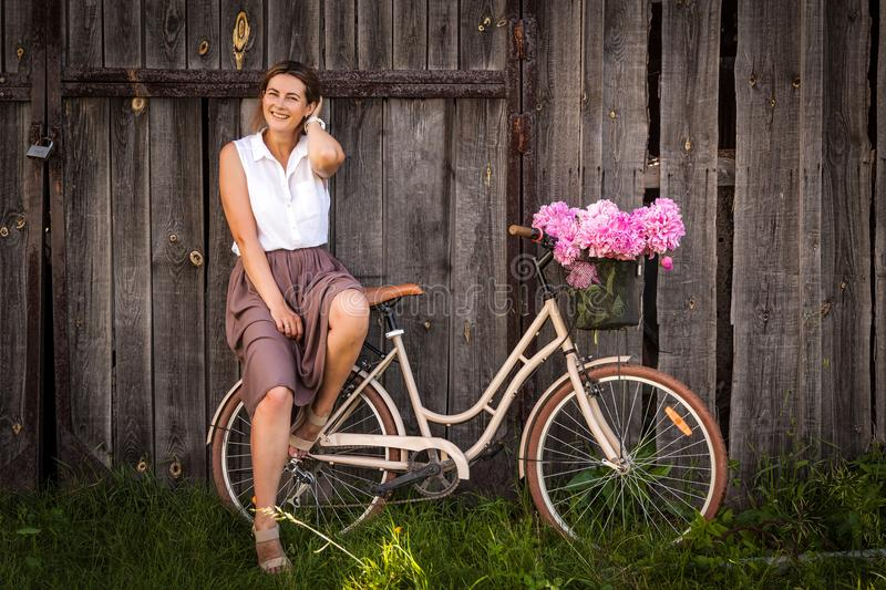 Woman with bouquet of peonies and bicycle. A young dark-haired woman in a white shirt in a beige skirt is holding a beautiful bouquet of pink peonies in a wicker stock images
