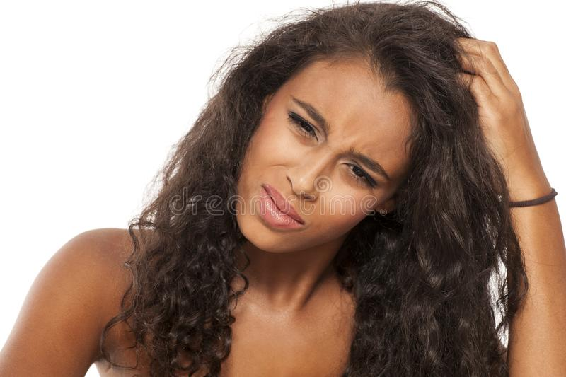 Itchy scalp. Young dark skinned girl has itching on her scalp royalty free stock photos