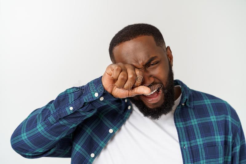 Young dark-skinned hipster guy wearing white shirt looking desperately down going to cry while found out about something. Horrorful. Crying man with bushy hair royalty free stock photos