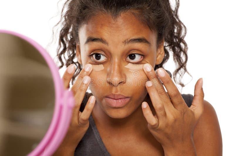 Women applying concealer. Young dark skinned woman applying concealer under her eyes with her fingers stock images