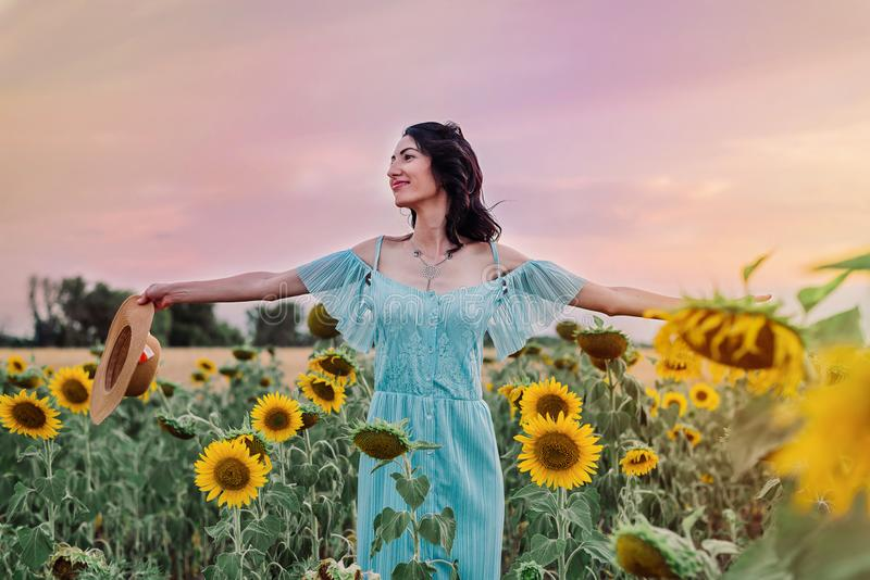 Young darkhaired woman in the sunflowers field is smiling and happy. Free life concept royalty free stock image