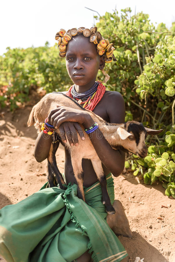 Young Dassanech girl with a goat. OMORATE, ETHIOPIA - AUGUST 17, 2015: unidentified girl from Dassanech tribe hold a little goat. She wear a beautiful hat made royalty free stock photo
