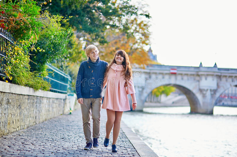 Young dating couple in Paris on a bright fall day. Walking together by the Seine, colorful autumn leaves in the background stock photography