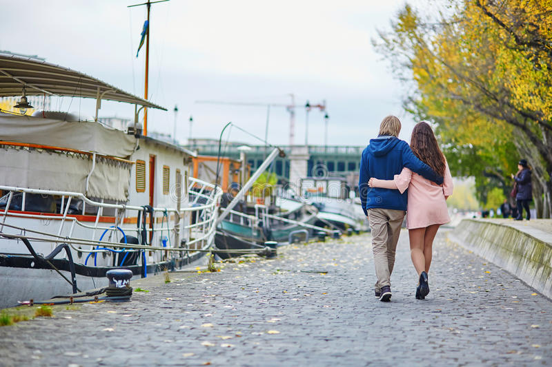 Young dating couple in Paris on a bright fall day. Walking together by the Seine, colorful autumn leaves in the background royalty free stock images