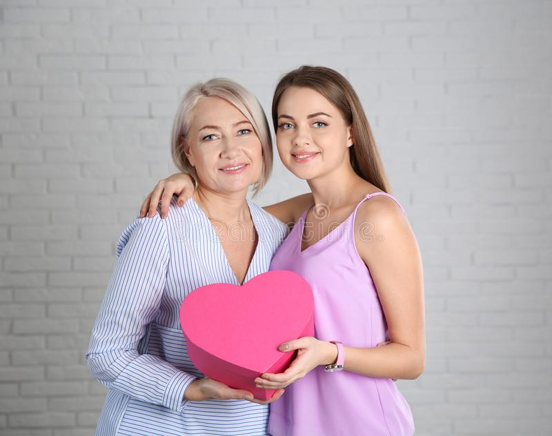 Young daughter congratulating her mature mother near wall. Happy Women`s Day stock image