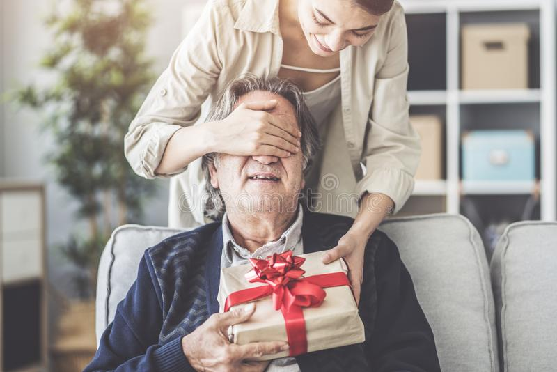 Young daughter gives her father a gift stock photo