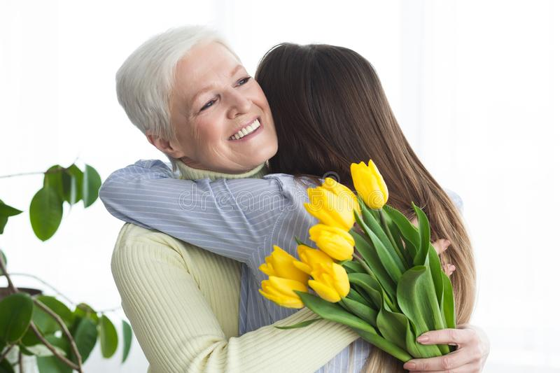 Young daughter giving flowers and hugging mother at home stock photo