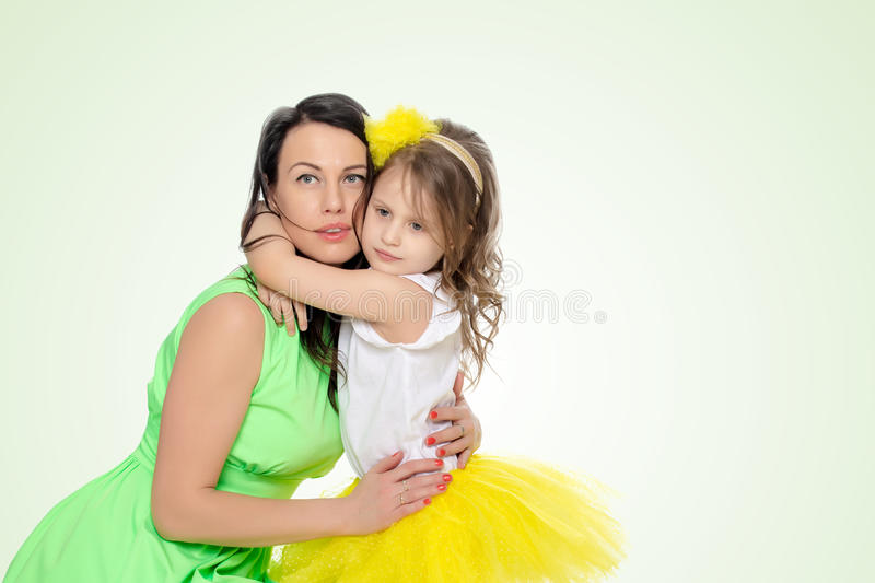 Young daughter hugs mother in the neck. stock photo