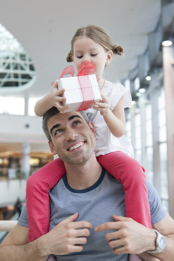 Young daughter sits on fathers shoulders and gives him a present stock image