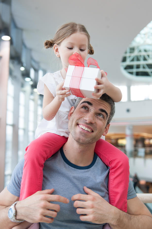 Young daughter sits on fathers shoulders and gives him a present royalty free stock image