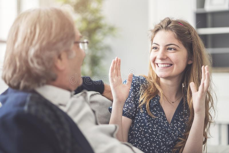Young daughter talking with her father stock photo
