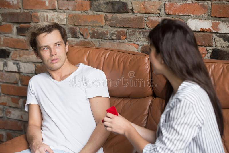 Decisive girl making marriage proposal to puzzled man. Young decisive girlfriend takes initiative in her hands, making marriage proposal to surprised boyfriend royalty free stock photo