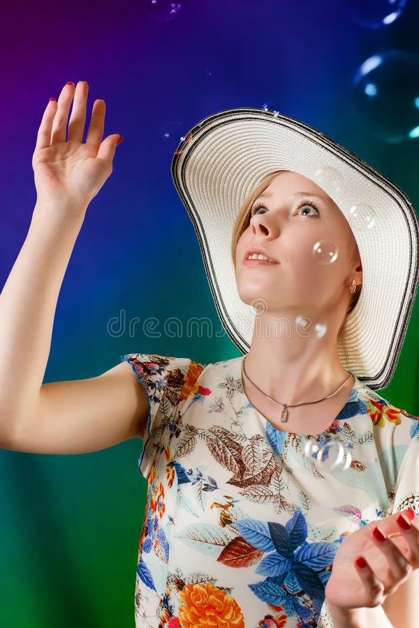 Young delighted woman with bubbles. Young delighted woman in summer dress and hat with bubbles. Looking up. On abstract colored background stock image