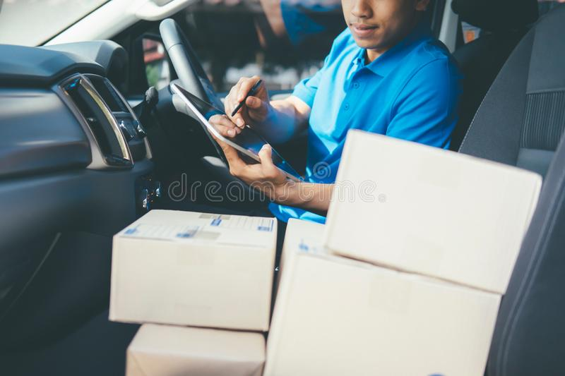 Young Delivery Man Checking Customer List On Tablet. royalty free stock image