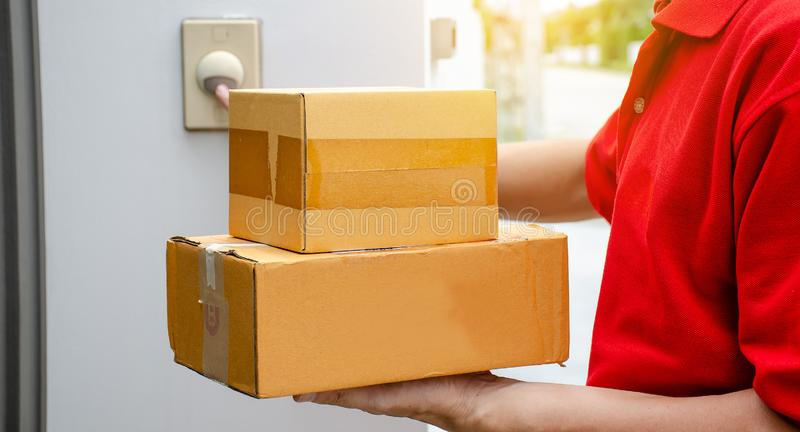 Young delivery man in red uniform standing with parcel post box press ring bell in front of the house to delivery of the good stock photos