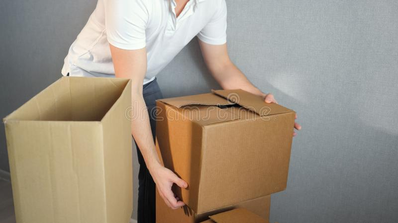 Young delivery service man carrying Boxes Into New Home On Moving Day stock images