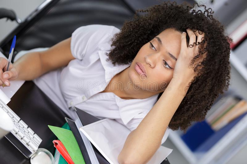 Young depressed businesswoman sitting at office desk stock image