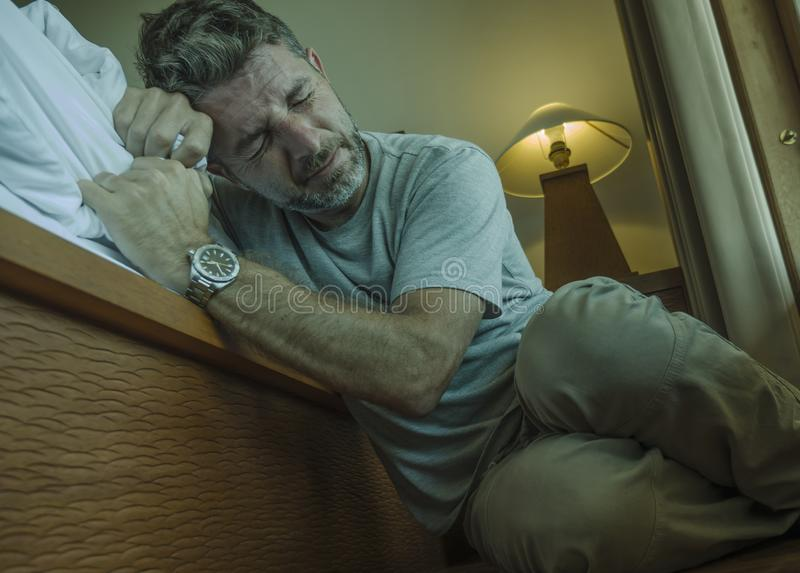 Young depressed and desperate man sitting on bedroom floor next to bed suffering depression and anxiety feeling overwhelmed and royalty free stock images
