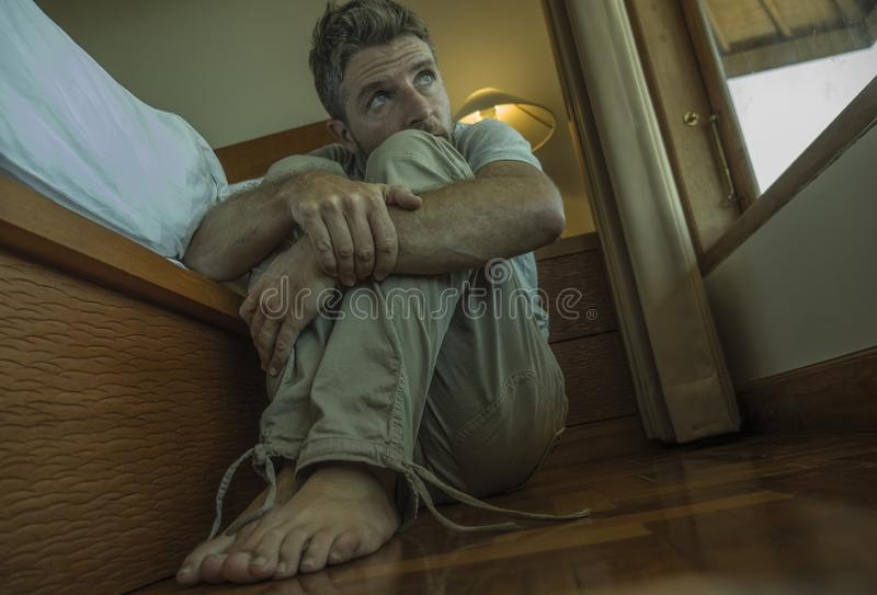 Young depressed and desperate man sitting on bedroom floor next to bed suffering depression and anxiety feeling overwhelmed and stock photo