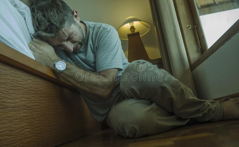 Young depressed and desperate man sitting on bedroom floor next to bed suffering depression and anxiety feeling overwhelmed and stock images