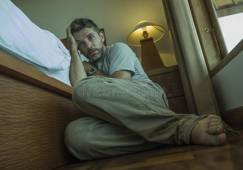 Young depressed and desperate man sitting on bedroom floor next to bed suffering depression and anxiety feeling overwhelmed and stock image
