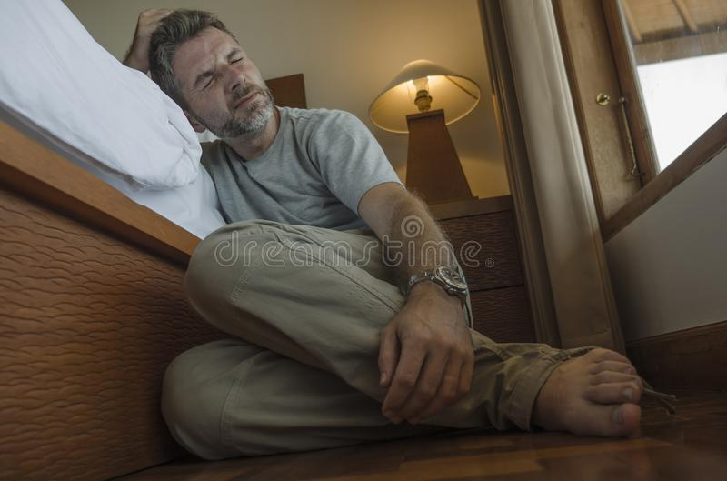 Young depressed and desperate man sitting on bedroom floor next to bed suffering depression and anxiety feeling overwhelmed and stock photography
