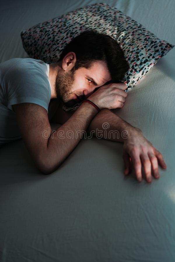 Young depressed man in pain on the bed. Young depressed man in pain lying in bed royalty free stock photography
