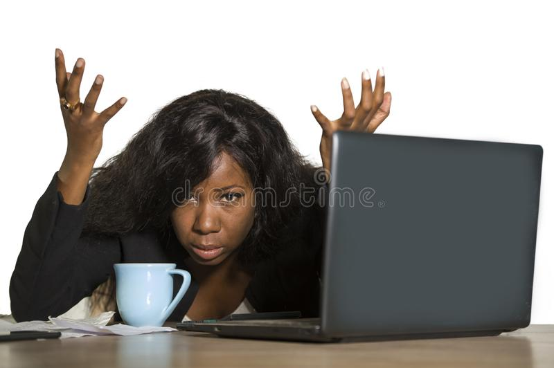 Young depressed and overwhelmed black African American business woman working frustrated at office computer desk feeling upset and. Overworked suffering stress royalty free stock photography