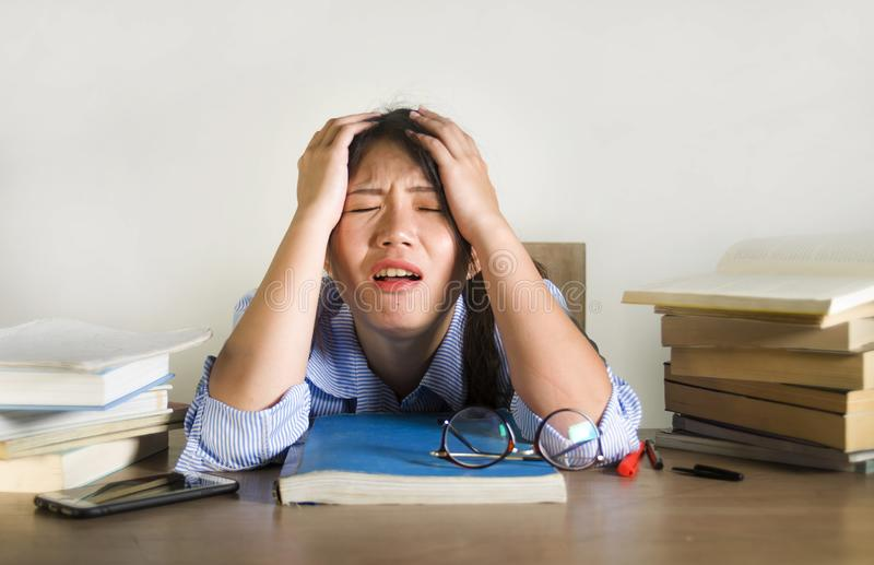 Young depressed and stressed Asian Chinese student girl working with laptop and book pile overwhelmed and frustrated preparing stock photos