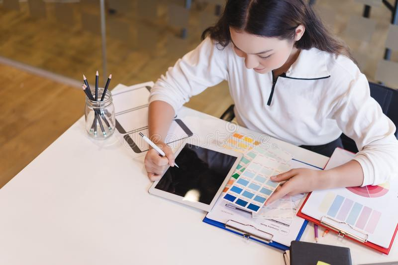 Young designer choosing color samples for design project,creative graphic design working desk. stock photo