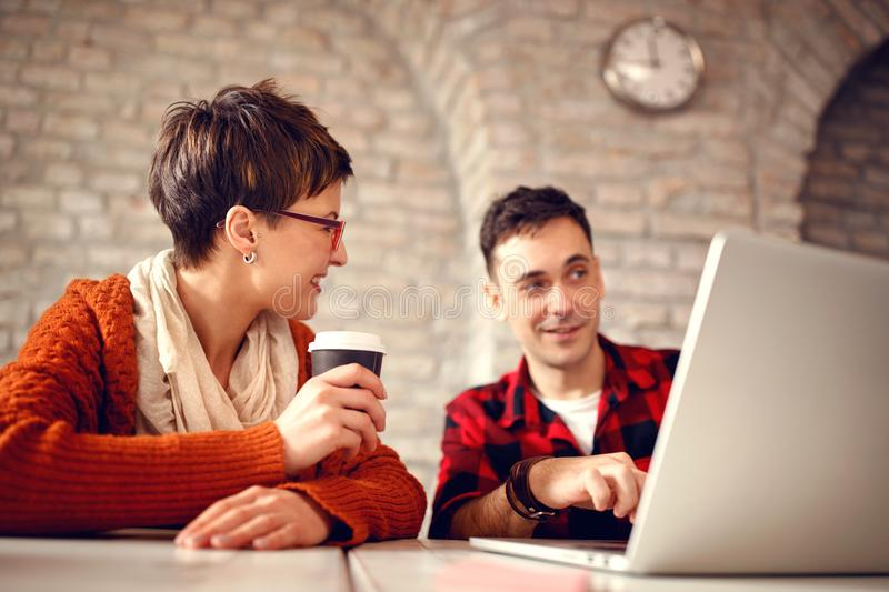 Young designer couple working late at computer stock photos