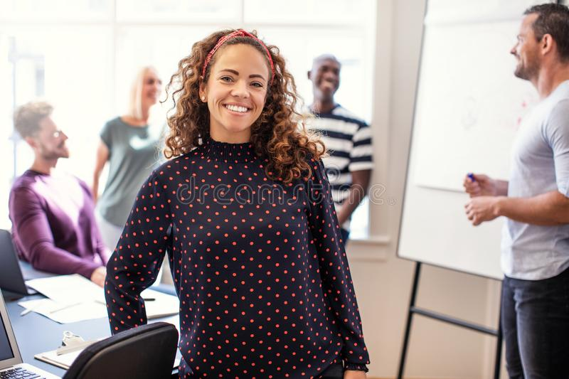 Young designer smiling with office colleagues in the background royalty free stock photos