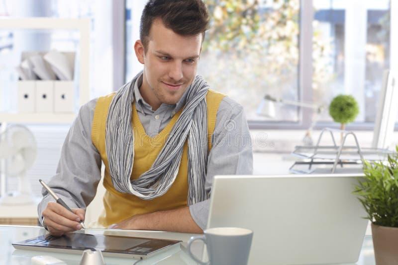 Young designer using drawing pad smiling
