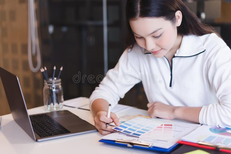 Young designer choosing color samples for design project,creative graphic design working desk. royalty free stock photos