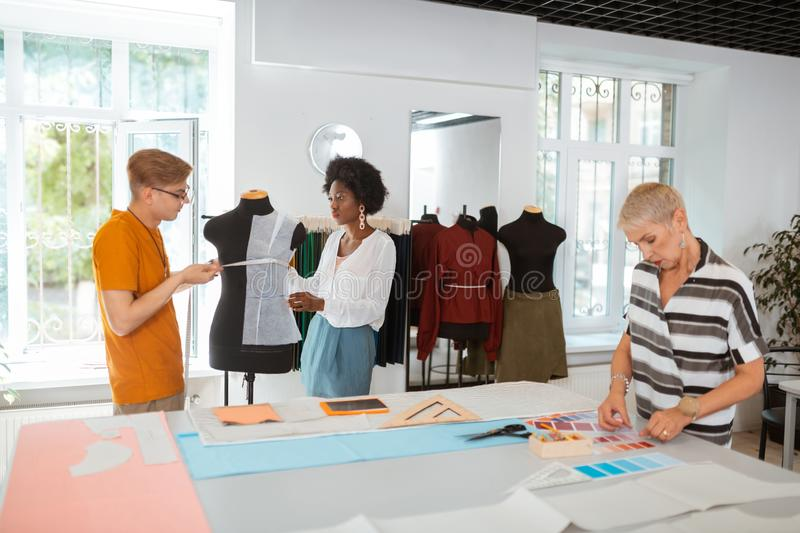 Young designers taking measurements on the tailor dummy. Creative team. Two young fashion designers taking measurements on the tailor dummy while their senior royalty free stock photo
