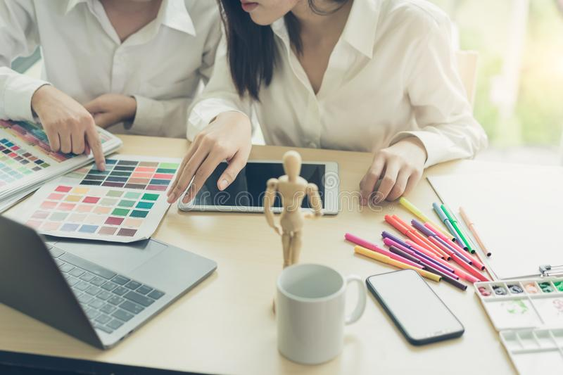Young designers teamwork working with color samples for selection on office desk royalty free stock images