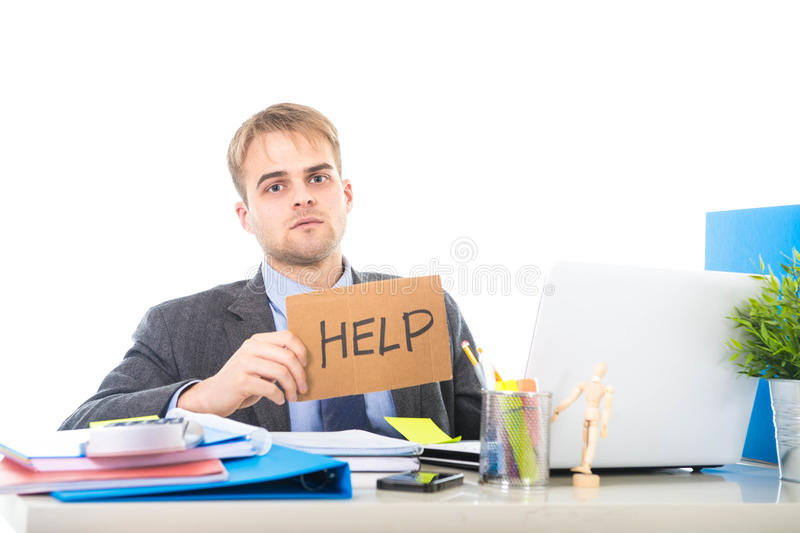 Young desperate businessman holding help sign looking worried suffering work stress at computer desk royalty free stock images