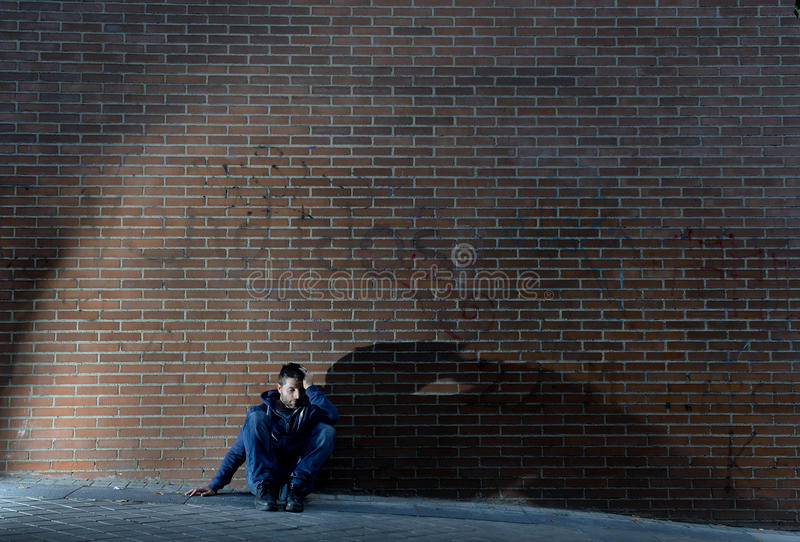 Young desperate jobless man who lost job lost in depression sitting on ground street corner royalty free stock images