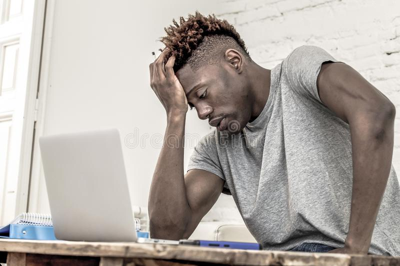 Young desperate and overwhelmed black afro American student man in stress at home working stressed with laptop computer worried an. Young desperate and stock images