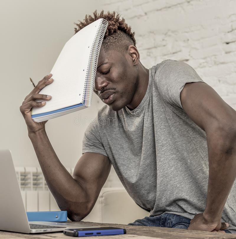 Young desperate and overwhelmed black afro American student man in stress at home working stressed with laptop computer worried an royalty free stock images