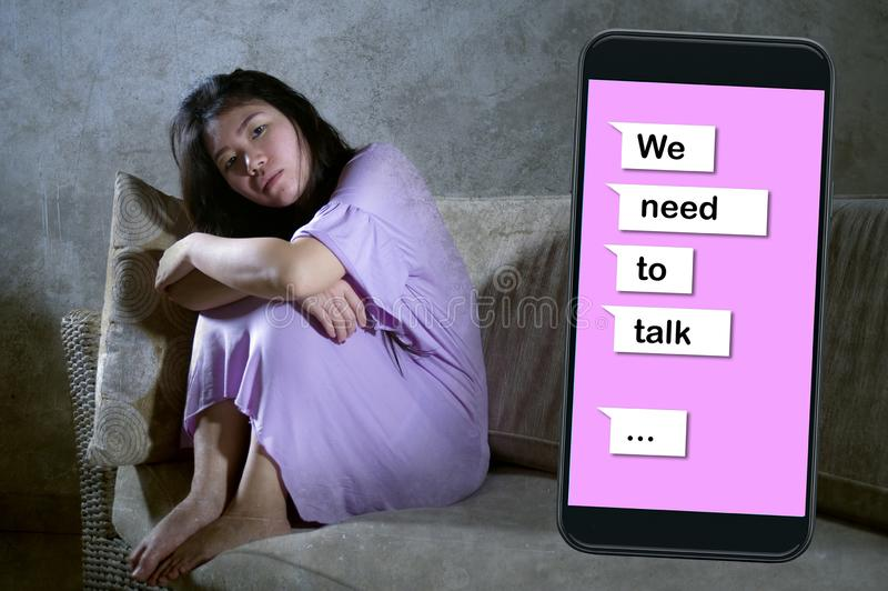Young desperate and sad Asian Korean woman feeling depressed suffering pain and broken heart composite with mobile phone online. Text in relationship problem royalty free stock photography