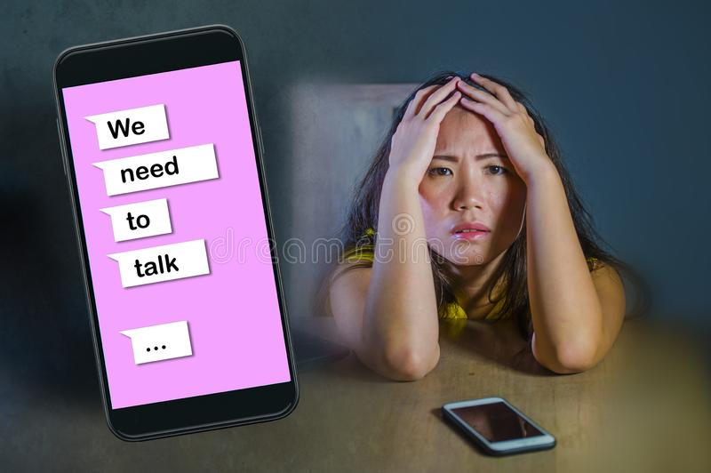 Young desperate and sad Asian Korean woman feeling depressed suffering pain and broken heart composite with mobile phone online. Text in relationship problem royalty free stock photo
