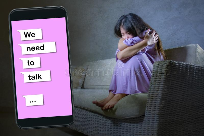 Young desperate and sad Asian Korean woman feeling depressed suffering pain and broken heart composite with mobile phone online. Text in relationship problem royalty free stock image