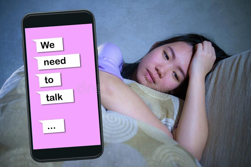 Young desperate and sad Asian Korean woman feeling depressed suffering pain and broken heart composite with mobile phone online. Text in relationship problem stock photo
