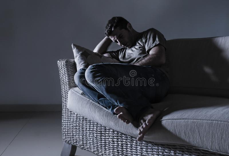 Young desperate sad and frustrated man grieving at home sofa couch suffering depression problem and anxiety crisis crying helpless stock photography