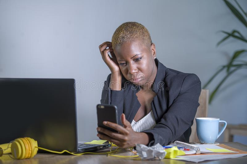 Young desperate and stressed african american business woman working at laptop computer desk at office suffering stress problem us. Ing mobile phone overwhelmed stock photos